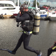 Lawrence in his scuba gear stepping off the dock