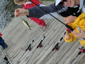 A child and his mother holding up their fishing rod with a perch caught on the line