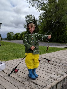 A young boy standing on the dock with his catch of a perch