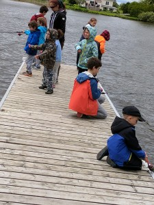 A group of young boys and girls on a dock fishing